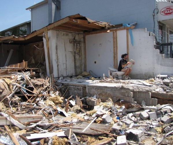 Image Un homme sur les toilettes d'une maison détruite