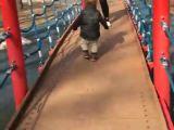 Un petit enfant tombe du pont dans un parc